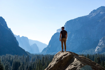 Hiker Standing On Top of Mountain Looking out at Vast Yosemite National Park