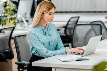 side view of young businesswoman working on laptop at workplace with notebook in office
