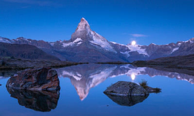 Fotomurales - The famous Matterhorn and the moon reflected in the Stellisee  before dawn. Zermatt, Switzerland.