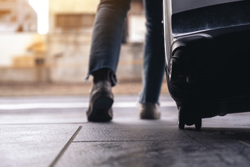 Closeup image of a woman's feet while traveling and dragging a black baggage in the outdoors