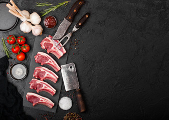 Fresh raw butchers lamb beef cutlets on stone board with vintage meat fork and knife and hatchet on black background.Salt, pepper and oil with tomatoes and garlic and barbeque sauce.Space for text