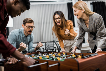 smiling multicultural business colleagues playing table football together in office