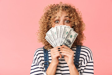 Photo of successful curly woman 20s holding fan of dollar money while standing, isolated over pink background