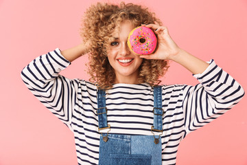 Image of content curly woman 20s wearing casual clothes eating donut while standing, isolated over pink background