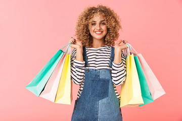 Image of glamorous curly woman 20s wearing casual clothes holding colorful shopping bags, isolated over pink background