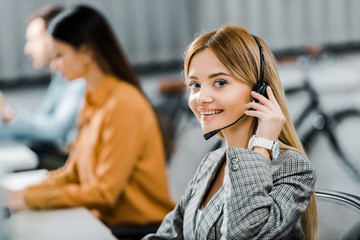 selective focus of smiling call center operator looking at camera in office
