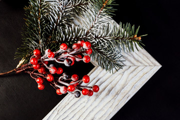 Picture frame with holly and pine branch on black background. Christmas concept.