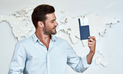 Happy young man with passports and tickets in the office of travel company