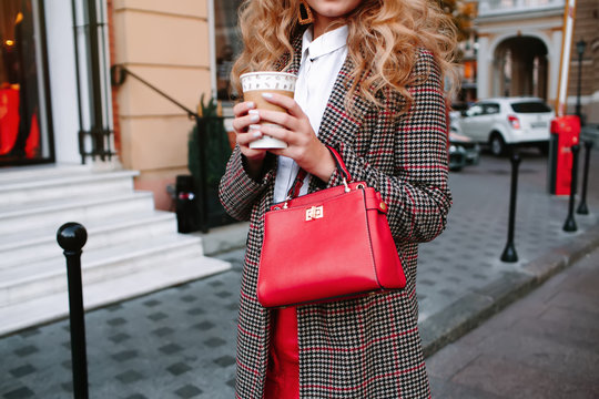 high fashion portrait of young elegant woman outdoor. Long trendy  coat, red bag and city wall background.Closeup details spring female casual street style outfit with luxury bag,trendy wool jacket