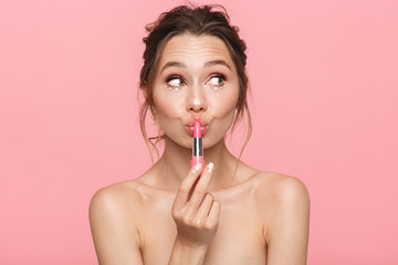 Shocked happy young woman posing isolated over pink wall background holding lipstick. Wall mural