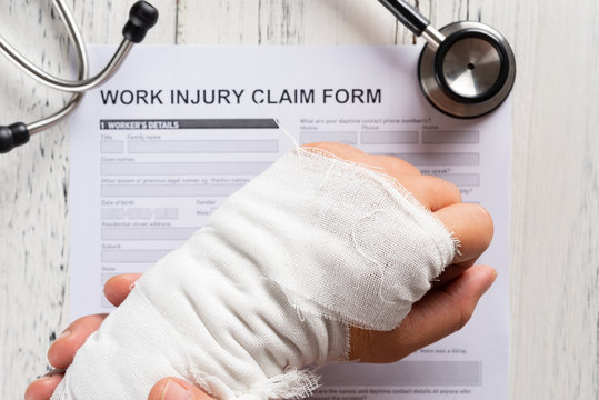 man holding his wrapped hand on top of a work injury claim form with stethoscope  medical and insurance concept