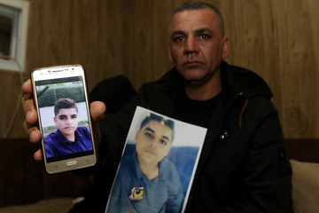 Kameran Mohammed, father of Miran, displays a picture of his son who died in a car accident, in Sulaimaniya