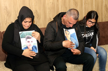 Parents of Miran, who died in a car accident, react while they hold his pictures at their home in Sulaimaniya