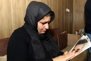 Nadia Marif, mother of Miran, holds a picture of her son who died in a car accident, in Sulaimaniya