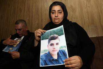 Parents of Miran, who died in a car accident, hold the pictures of their son at their home in Sulaimaniya