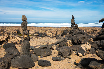 Photo sur Plexiglas Zen pierres a sable Stones pyramid on sand symbolizing zen, harmony, Stone balancing