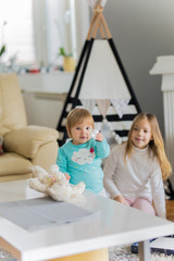 Baby girl and her sister playing in living room in front of kid's tent