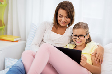 people, family and technology concept - happy mother and daughter with tablet pc computer and earphones at home
