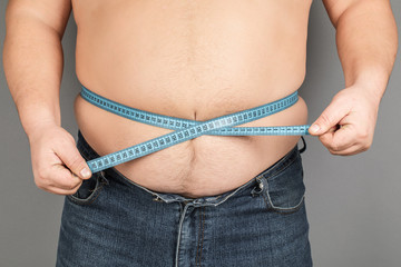 A man measures his fat belly with a measuring tape. on a gray background.