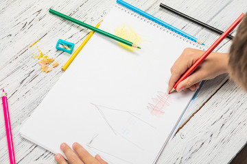 Kids drawing and lots of pencils for drawing on wooden background.