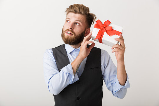 Handsome young bearded man standing isolated over white wall background holding present gift box.
