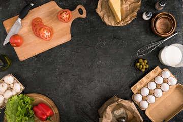 chopped tomatoes on cutting board and pizza ingredients on grey background with copy space