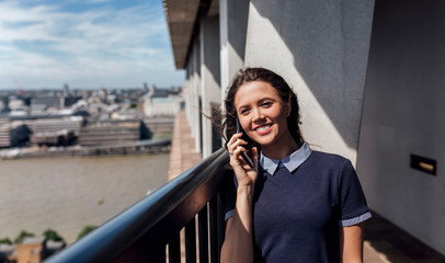 UK, London, smiling woman on the phone on a roof terrace