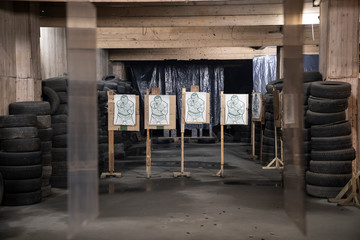 Boards with male likeness as targets in an indoor shooting range