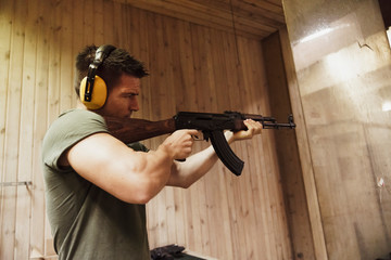 Man aiming with a rifle in an indoor shooting range