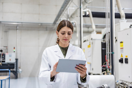 Woman checking manufacturing machines in high tech company, using digital tablet