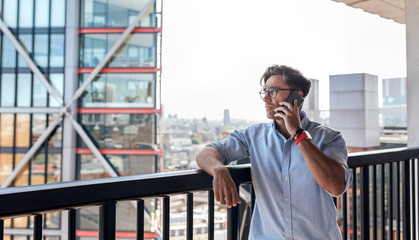 UK, London, man on the phone on a roof terrace