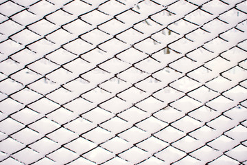 Abstract Snow winter pattern, background. Metal grid with white sticking snow