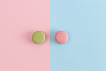Pink and green macarons on divided background.