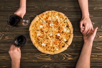 cropped view of couple holding hands and glasses of red wine while eating pizza on wooden table