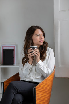 Thoughtful young woman with brunette hair having coffee at home