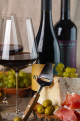 red wine in glasses, cheese, olives, ham and grapes. Composition
