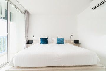 A white bedroom with a wooden bed, bed linen and a pillow with white cloak. good for relaxing The white room makes the room feel comfortable.