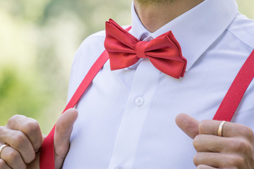 The groom in a shirt with a red bow tie and in suspenders