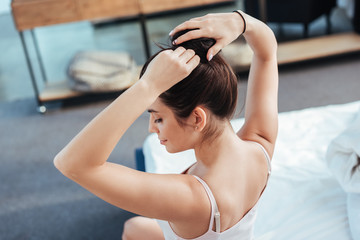high angle view of girl collecting ponytail while sitting on bed during morning time at home