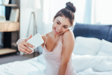happy girl taking selfie on smartphone while sitting on bed during morning time at home