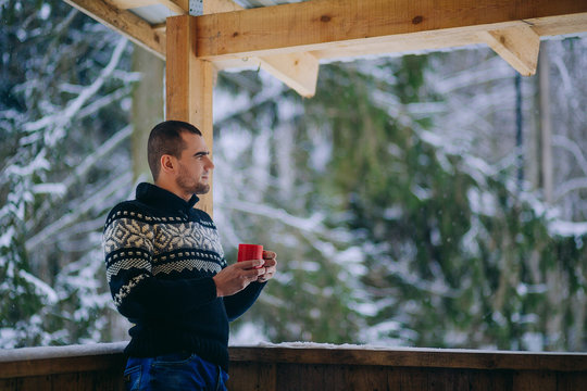 Young guy stands on the porch of the House and drinking hot tea in winter
