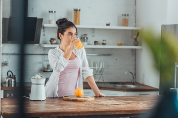 Poster Juice young woman drinking orange juice in kitchen during morning time at home