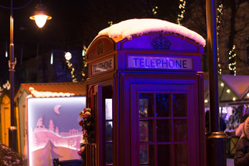 English red classic telephone booth at night time with many light illumination in urban street environment Christmas winter holidays season time