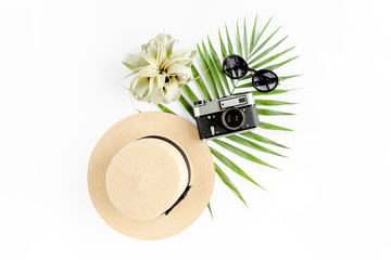Traveler accessories on white background with retro camera, straw hat, sunglasses, and tropical palm leaf. Travel concept background. Flat lay. Top view