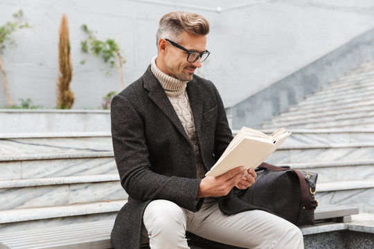 Handsome man wearing jacket reading a book