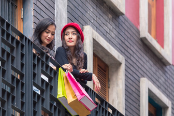 A couple beautiful charming joyful asian full of colourful shopping bags point there fingers while relax at building terrace at super store. Friendship shopping at weekend concept.