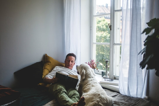 Senior man lying with dog while reading book on bed by window at home