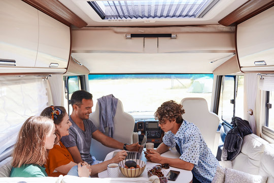 High angle view of family looking at laptop while sitting in camper van