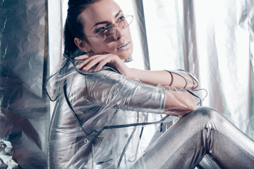 attractive young woman posing in trendy eyeglasses, silver bodysuit and raincoat on metallic background