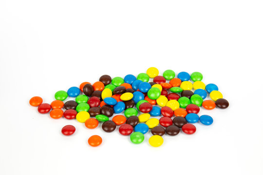 Colorful chocolate M&Ms in and out of focus on white background